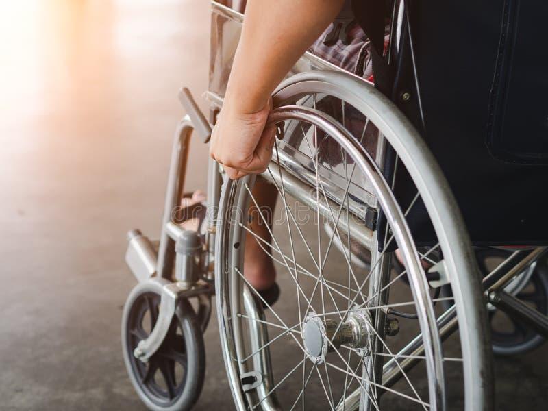 Een gehandicapte mens zit in een rolstoel Hij houdt zijn handen stock fotografie