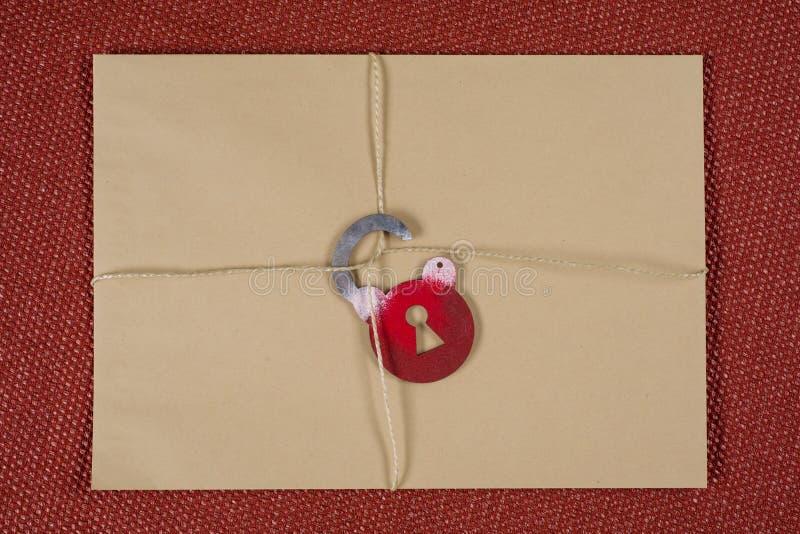Een geheime envelop, een pakket bond met een kabel, met symbolisch slot Open het slot stock afbeeldingen
