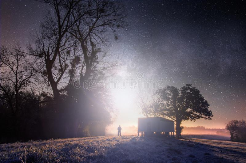 Een geheimzinnig concept geeft van een eenzame die mens uit tegen een helder licht op een de wintersnacht wordt gesilhouetteerd i royalty-vrije stock fotografie