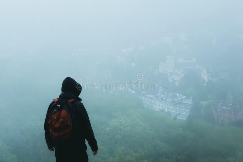 Een geheimzinnige wandelaar met een kap met rugzak, die downfrom een heuvel op een stad kijken Voor een foogy, regenachtige de zo royalty-vrije stock foto's
