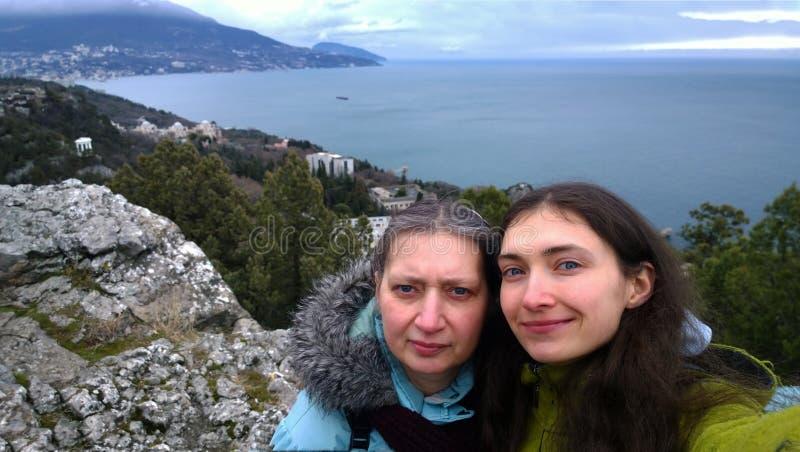 Een gekweekte vrouw met haar jonge dochter die selfies op de berg tijdens de reis doen stock foto