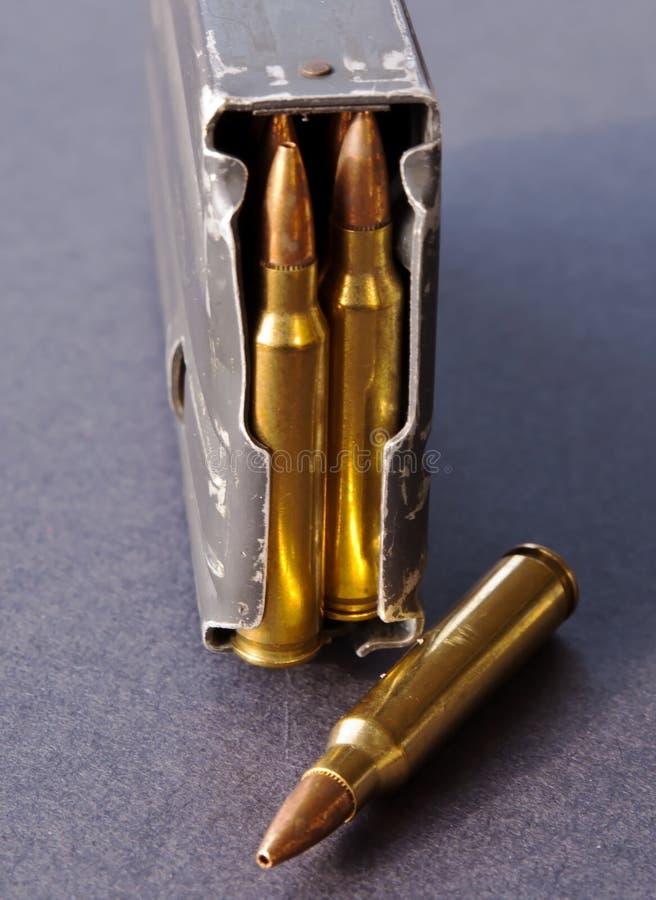 Een geladen geweertijdschrift met 223 kaliberkogels met één enkele holle puntkogel naast het stock afbeelding
