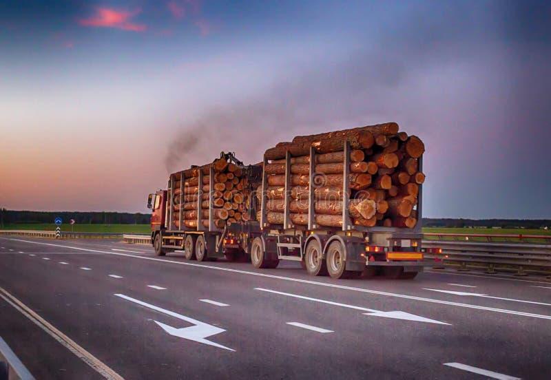 Een geladen houtvrachtwagen vervoerden houtlogboeken met een overbelasting op de weg, zwarte rook Het concept vervoer van hout stock foto