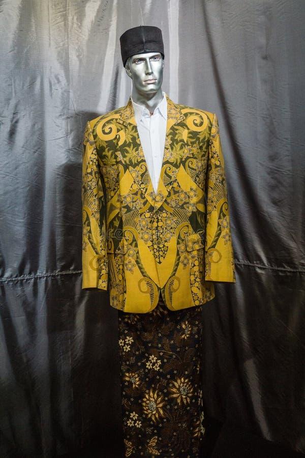 Een Gele die kostuum en een Sarong met batikpatroon in de foto wordt getoond van het Batikmuseum in Pekalongan Indonesië wordt ge royalty-vrije stock afbeeldingen