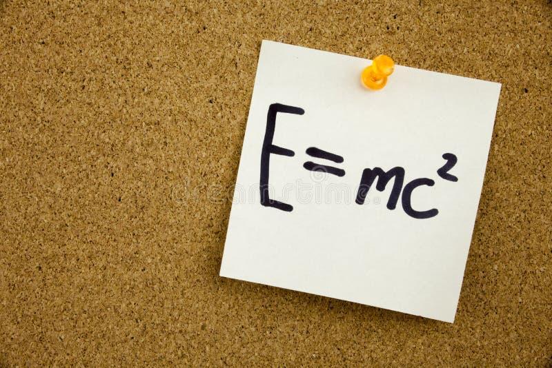 Een gele kleverige nota die, titel, inschrijvingsvergelijking E GELIJKE MC2 in zwart Ext. op een kleverige die nota schrijven aan stock afbeeldingen
