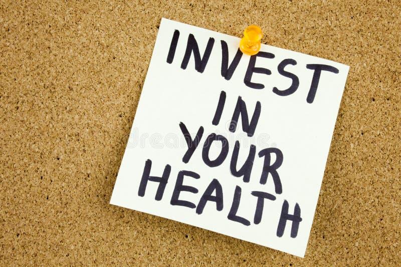 Een gele kleverige notapost-it die, titel, inschrijving investeert in uw gezondheid in zwart Ext. op een kleverige die nota schri stock afbeelding