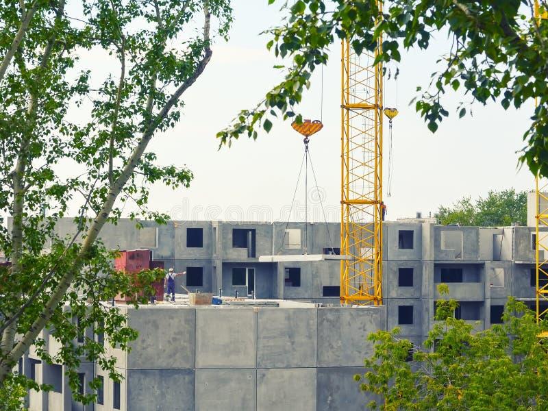Een gele kraan heft een concreet paneel op een woningbouw op Een arbeider zonder een bouwvakker - een schending van veiligheidsve stock fotografie