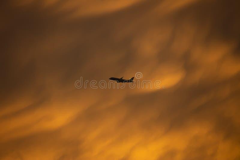 Een gele onstuimigheidswolk met silhouetvliegtuig die door vliegen stock foto
