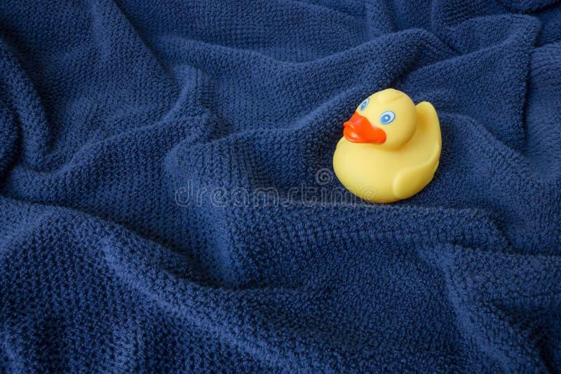 Een gele rubbereend op blauwe golvende handdoek stock afbeelding