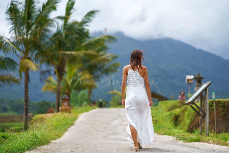 Een gelooide vrouw in een witte kleding loopt vooruit op de weg De mening van de rug Op de achtergrond, een berg in de mist en stock foto