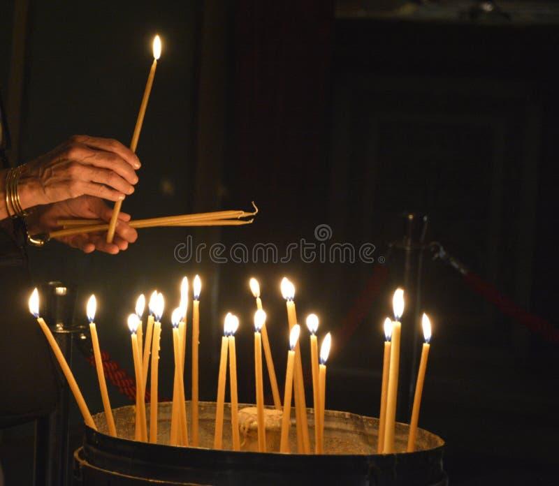 Een gelovige steekt kaarsen bij de Kerk van het Heilige Grafgewelf, Jeruzalem aan stock afbeelding