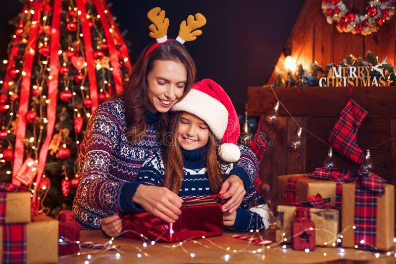 Een gelukkig familiemoeder en een kind pakken Kerstmisgiften in royalty-vrije stock fotografie