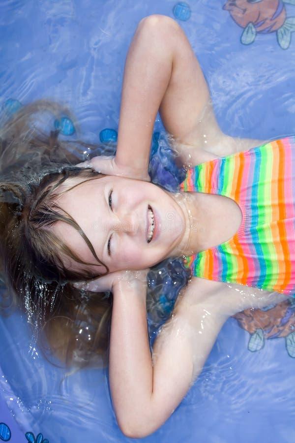 Een gelukkig meisje dat in pool van water legt. stock foto