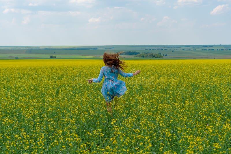 Een gelukkig meisje met lange haarlooppas over een geel bloemgebied Het haar ontwikkelt zich stock fotografie