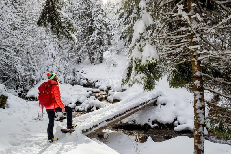 Een gelukkig meisje, met een rood jasje en een rode rugzak, die een houten brug kruisen, tijdens een de winter wandelingsreis royalty-vrije stock foto