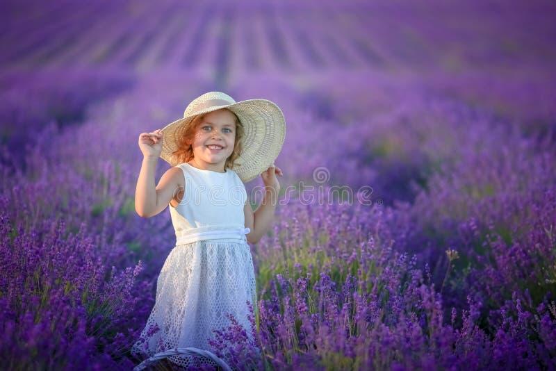 Een gelukkig meisje op een gebied die een mand met lavendel houden bloeit stock afbeeldingen