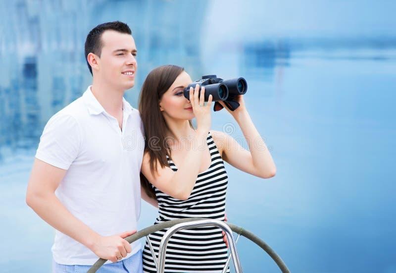 Een gelukkig paar op een boot die door verrekijkers kijken stock fotografie