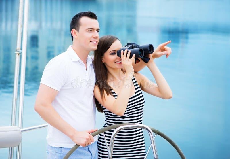 Een gelukkig paar op een boot die door verrekijkers kijken stock afbeeldingen