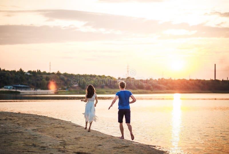 Een gelukkig paar op een zonsondergangachtergrond die op het water lopen Een man loopt na een vrouw in een kleding op een rivier  royalty-vrije stock afbeeldingen