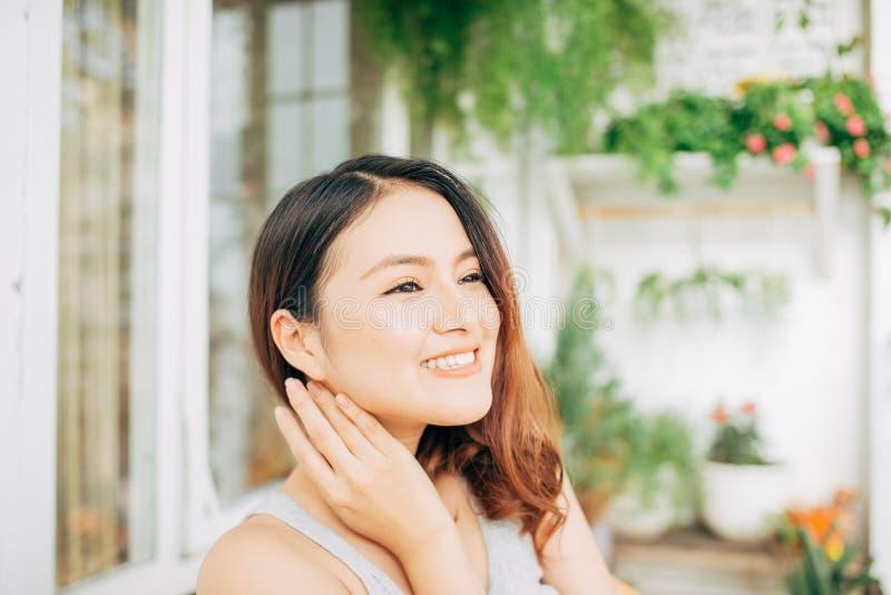 Een gelukkige Aziatische vrouwenzitting op een stoel in balkon in de ochtend stock foto's