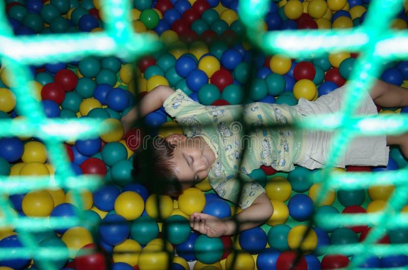 Een gelukkige baby ligt op plastic ballen stock afbeeldingen