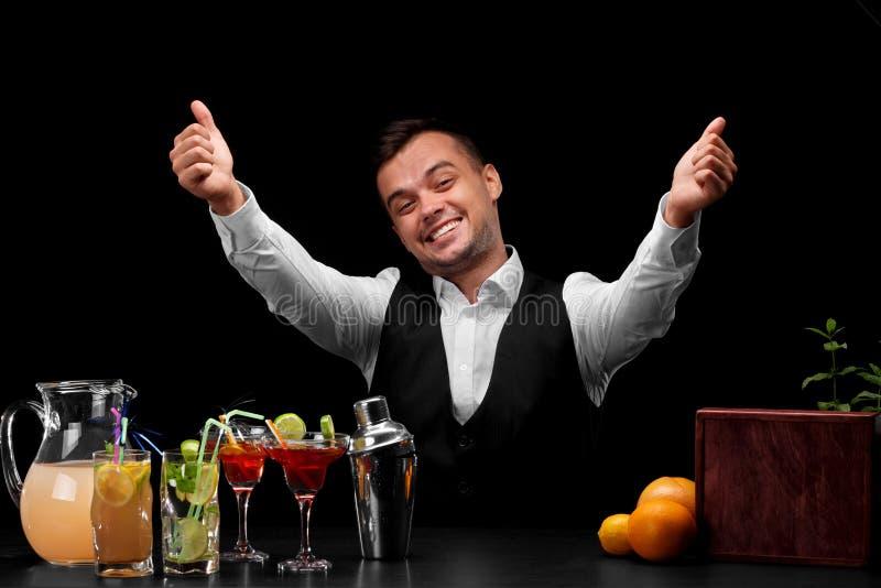 Een gelukkige barman in een klassiek kostuum op een zwarte achtergrond Vele kleurrijke ingrediënten voor cocktails op een lijst royalty-vrije stock foto's