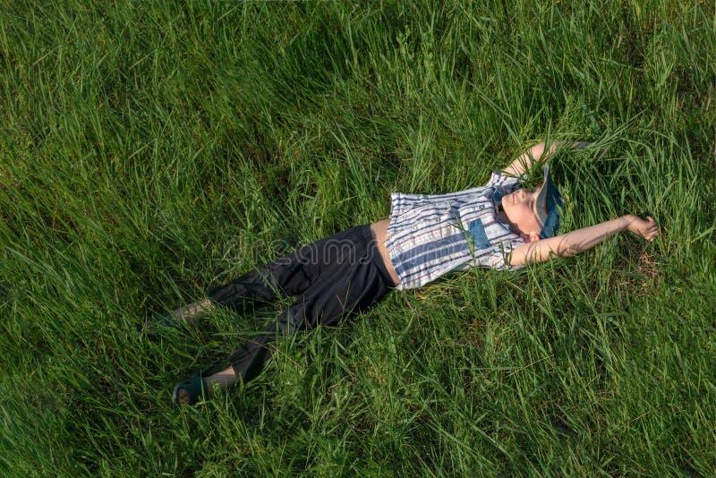 Een gelukkige en blije jongen ligt op het gras, onbezorgde kinderjaren stock foto's