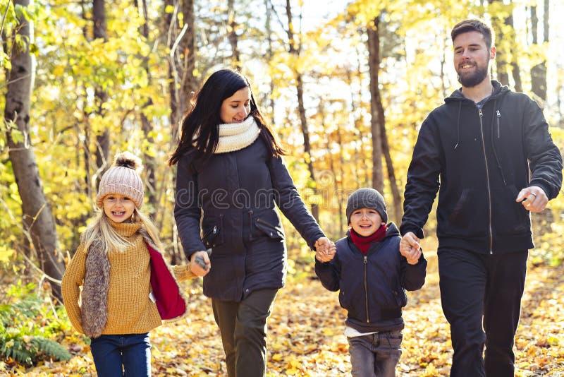 Een Gelukkige familie die in mooi de herfstpark rusten stock fotografie