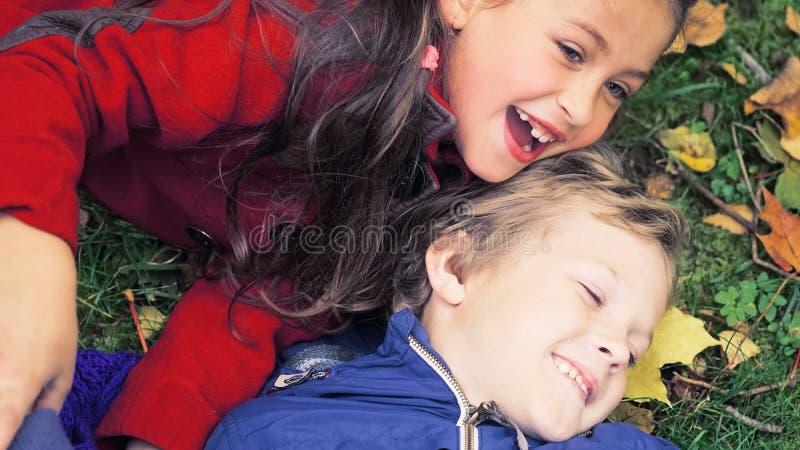 Een gelukkige familie die pret in het park in de herfst hebben Familie, liefde, gelukconcept En broer en zuster die koesteren lig royalty-vrije stock foto