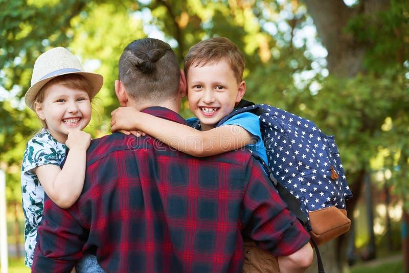 Een gelukkige familie van vader en kinderen De papa is op de handen van kinderen in lage school Vader, zoon en dochter in de herf royalty-vrije stock foto's