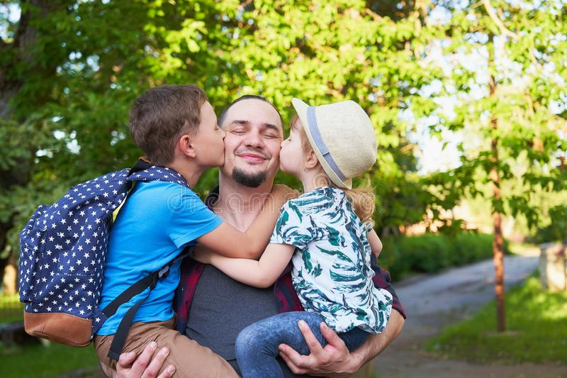 Een gelukkige familie van vader en kinderen De papa is op de handen van kinderen in lage school Vader, zoon en dochter in de herf stock fotografie