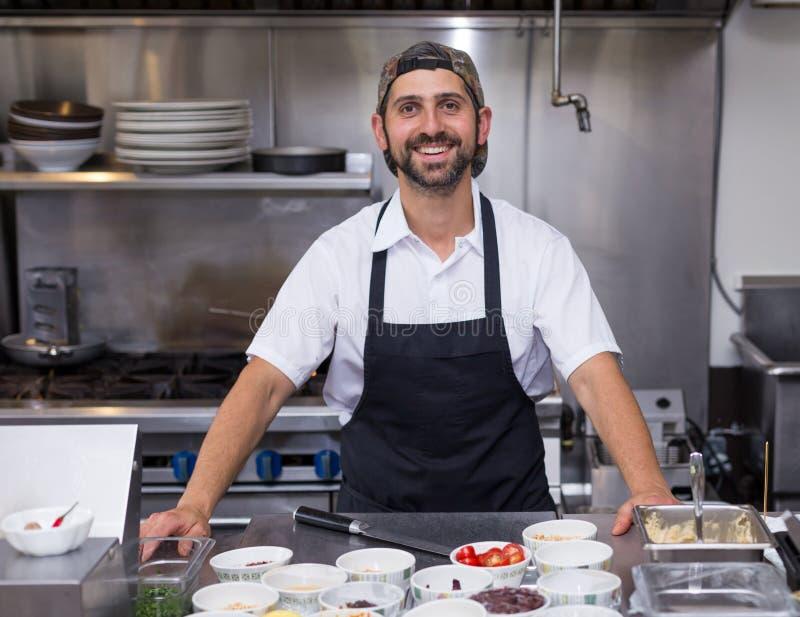 Een gelukkige glimlachende chef-kok die zich voor zijn voedselpost bevinden in een restaurantkeuken royalty-vrije stock afbeelding