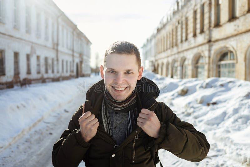 Een gelukkige glimlachende mens die bont het in warme sjaal stellen in de stad dragen stock afbeelding