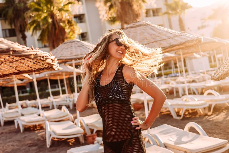 Een gelukkige glimlachende vrouw in een transparante uniformjas die haar lang haar in het de contouren aangegeven van zonsonderga stock foto