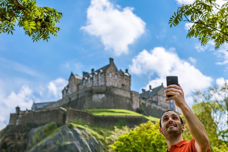 Een gelukkige jonge mensentoerist bij het Kasteel die van Edinburgh selfie op m nemen stock foto's