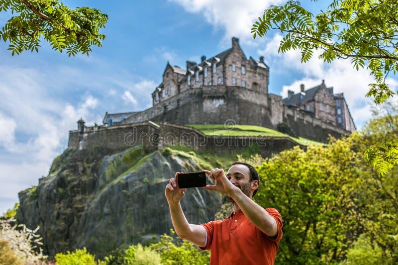Een gelukkige jonge mensentoerist bij het Kasteel die van Edinburgh selfie op m nemen stock afbeelding