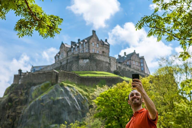 Een gelukkige jonge mensentoerist bij het Kasteel die van Edinburgh selfie op m nemen stock foto