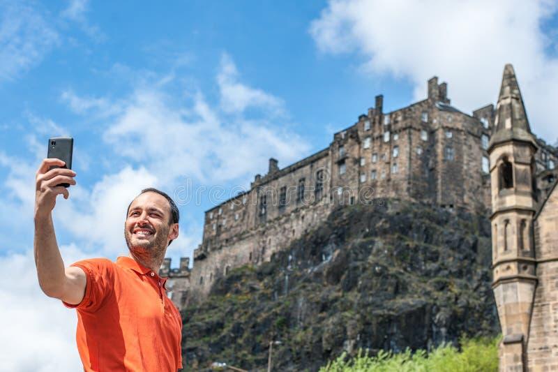 Een gelukkige jonge mensentoerist die selfie bij het Kasteel van Edinburgh nemen met royalty-vrije stock foto's
