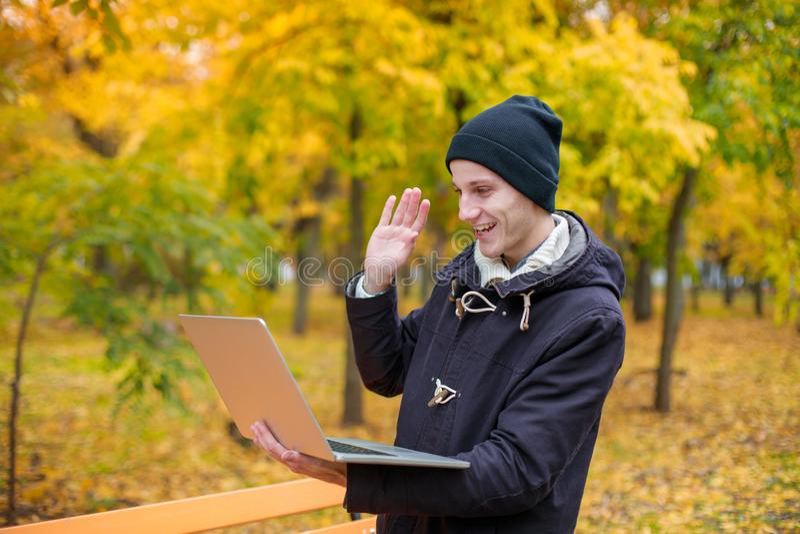 Een gelukkige kameraad met iemand via videomededeling over laptop en het golven van van hem dienen een de herfstpark in royalty-vrije stock fotografie