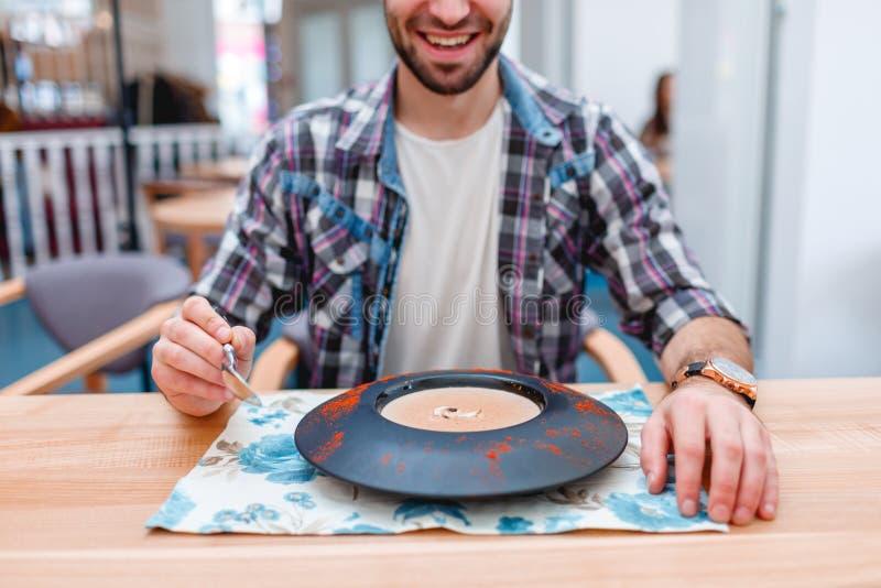 Een gelukkige kerel, dineert in een koffie etend champignonsoep stock foto