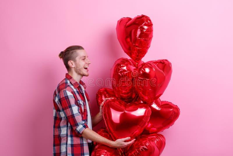 Een gelukkige kerel is gelukkig met een stapel van heliumballen in de vorm van een hart Roze achtergrond stock afbeeldingen