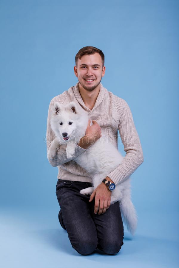 Een gelukkige kerel houdt a puppy samoyed Op een blauwe achtergrond stock fotografie