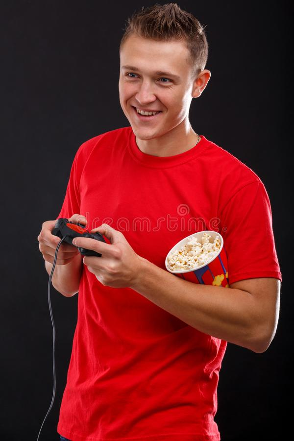 Een gelukkige kerel met rente die de console spelen die een spelbedieningshendel en een glas popcorn houden Zwarte achtergrond royalty-vrije stock afbeeldingen