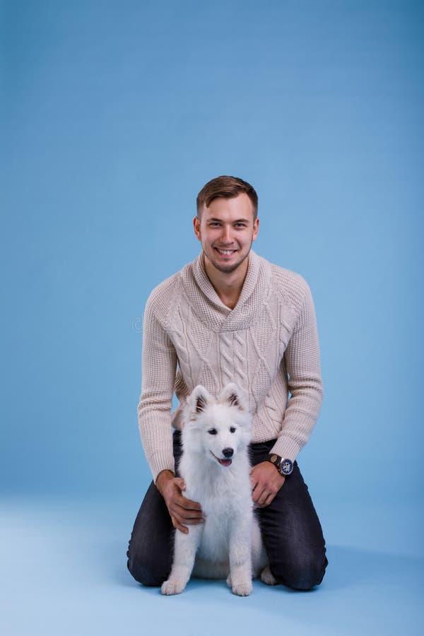 Een gelukkige kerel zit en speelt met een leuk Samoyed-puppy Op een blauwe achtergrond royalty-vrije stock fotografie