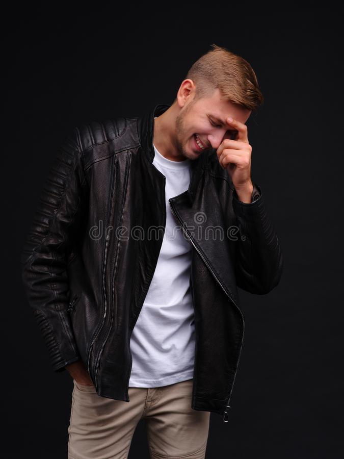Een gelukkige kerel in een zwart jasje lacht met zijn hand op zijn hoofd royalty-vrije stock foto's