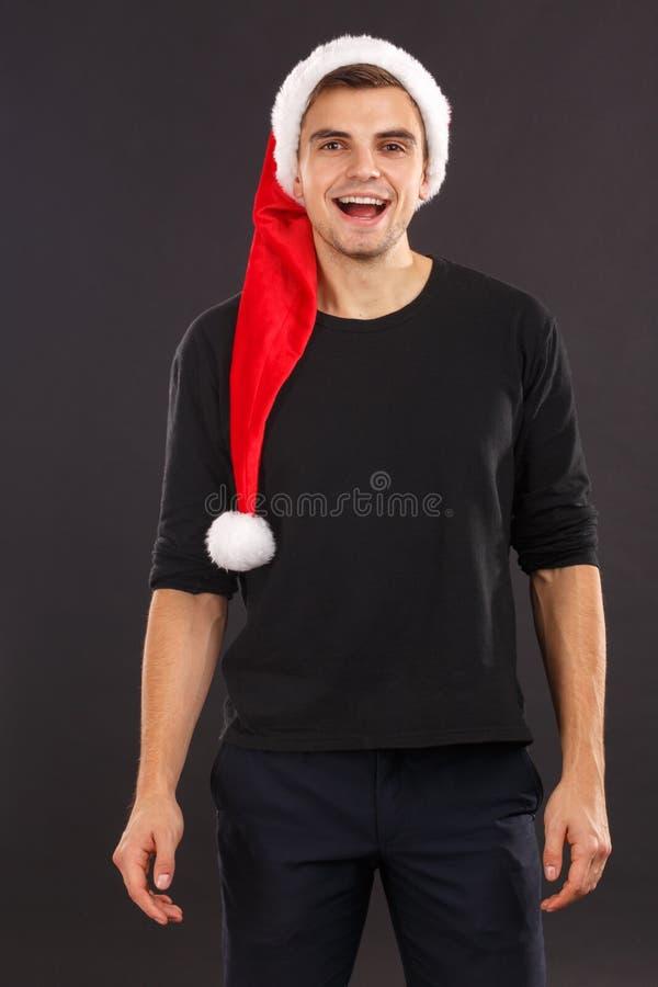 Een gelukkige kerel in een zwart sweatshirt en Kerstman ` s GLB glimlacht Op een zwarte achtergrond binnen royalty-vrije stock afbeeldingen