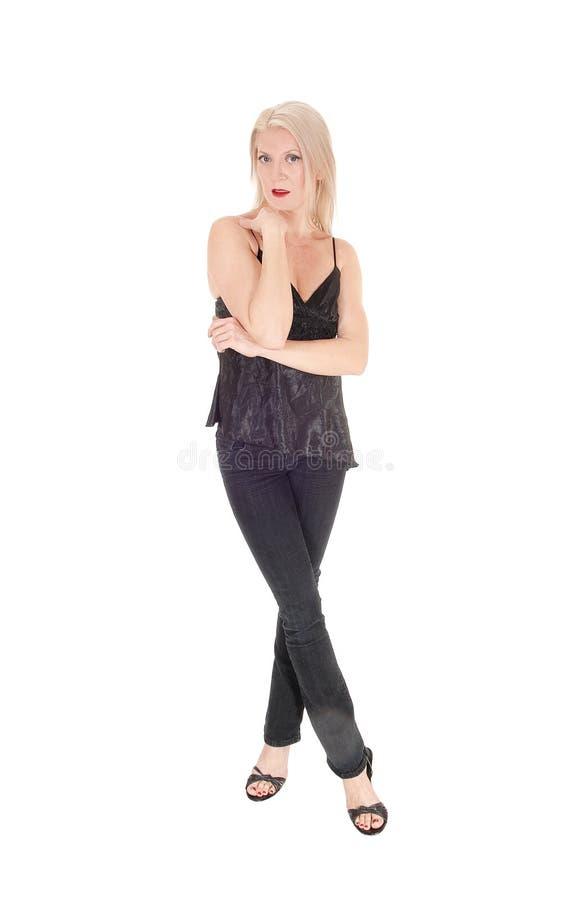 Een gelukkige kijkende blonde vrouw die zich in zwarte gekruiste uitrustingsbenen bevinden royalty-vrije stock fotografie