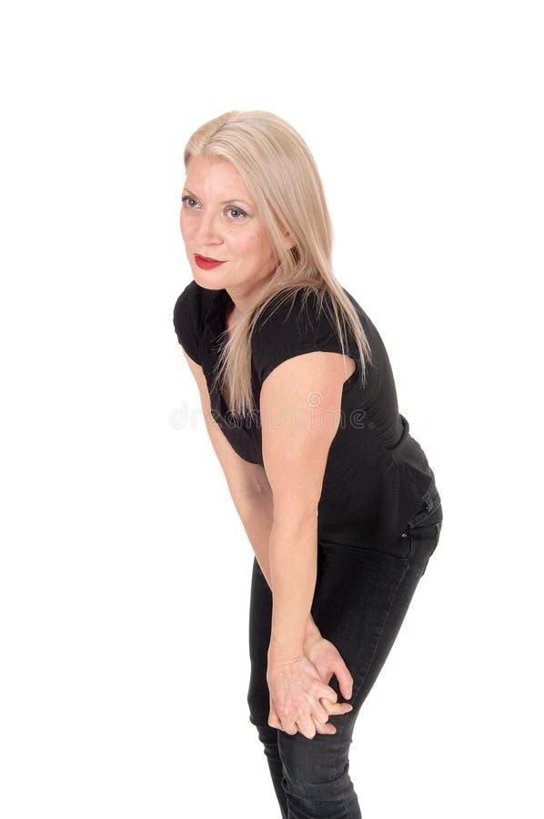 Een gelukkige kijkende blonde vrouw die zich in zwarte uitrusting bevinden royalty-vrije stock foto's