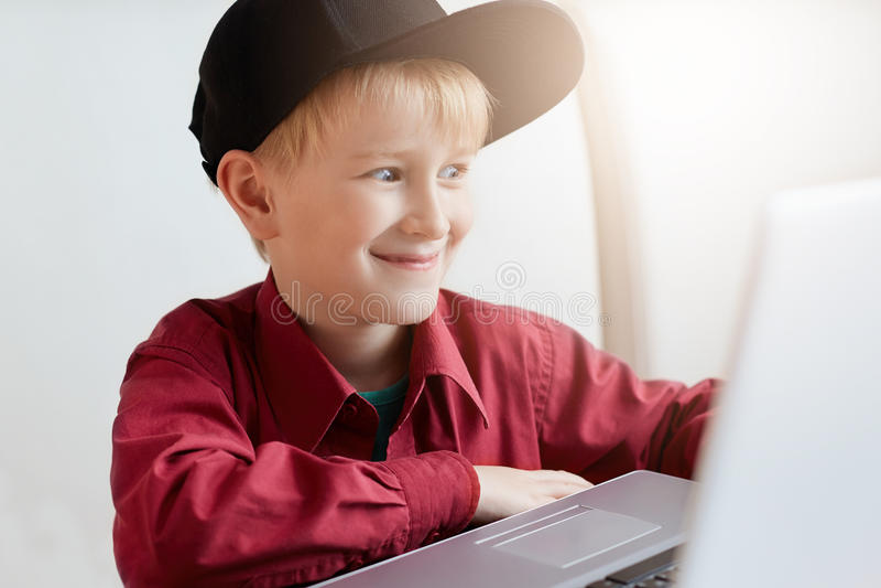 Een gelukkige kleine jongen die in in kleren tijdens lunch bij moderne koffie ontspannen, die voor open laptop zitten die expres  royalty-vrije stock afbeeldingen
