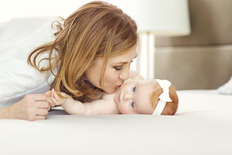 Een gelukkige kleinzoon van de grootmoeder kussende baby op het bed royalty-vrije stock fotografie